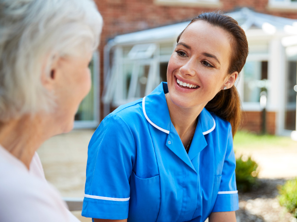 Senior woman sitting on a bench, talking with nurse in a retirement home