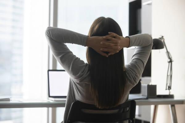 Woman at desk with a laptop, relaxing with her hands behind her head
